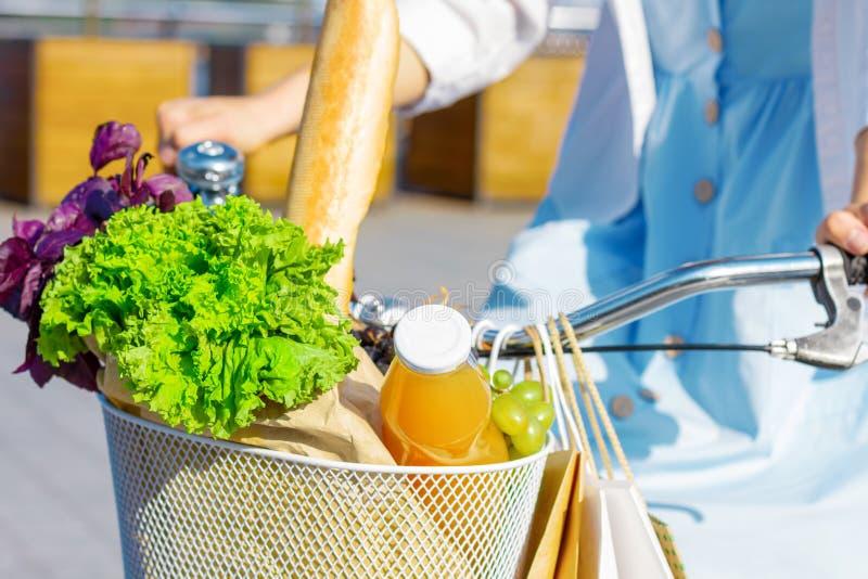 Kobieta iść na piechotę w błękit sukni na białym bicyklu z koszykowy pełnym warzywa obraz royalty free