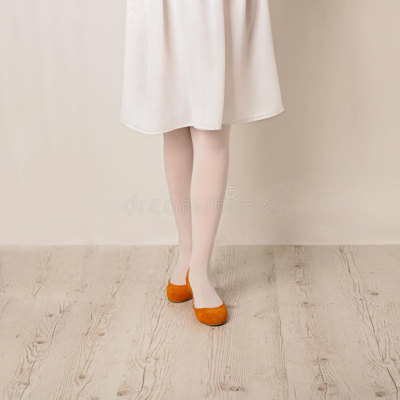 Kobieta iść na piechotę w białych rajstopy, spódnicy i baleta mieszkaniach na białym b, obrazy stock