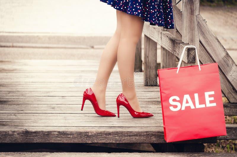 Kobieta iść na piechotę w eleganckich czerwonych butach z piętami na drewnianym moscie a obraz stock