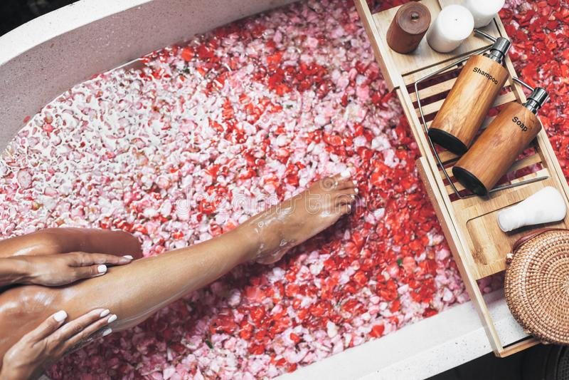 Kobieta iść na piechotę w wannie z kwiatów płatkami i piękno produktami na drewnianej tacy obrazy royalty free