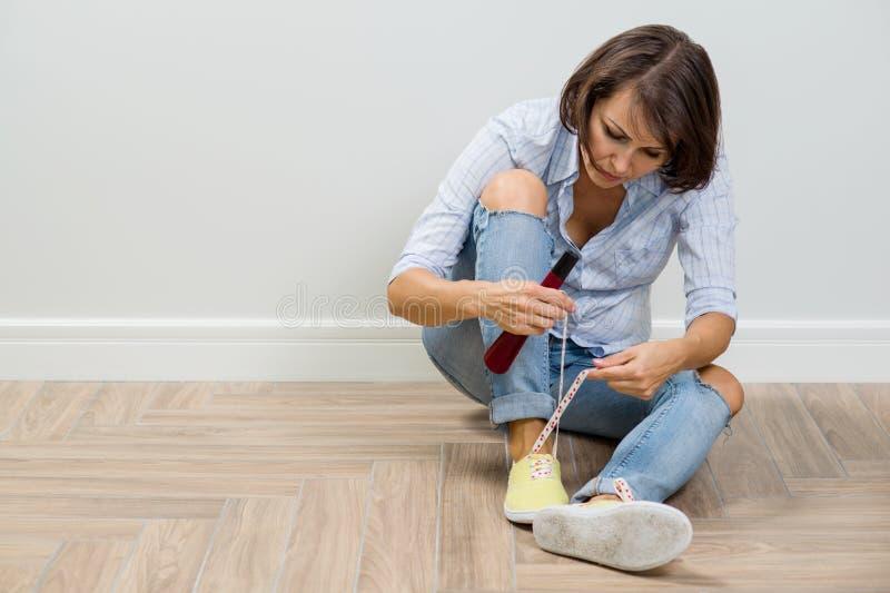 Kobieta iść opuszczać dom, kuje sneakers, wiąże shoelaces obrazy stock