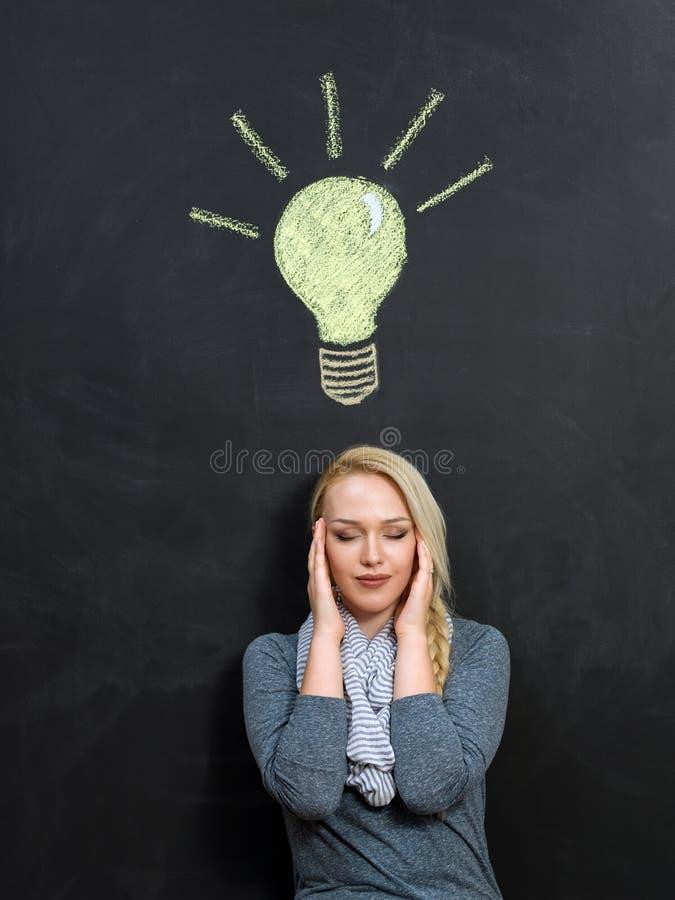 Kobieta i żarówka rysujący w kredzie na blackboard obrazy stock