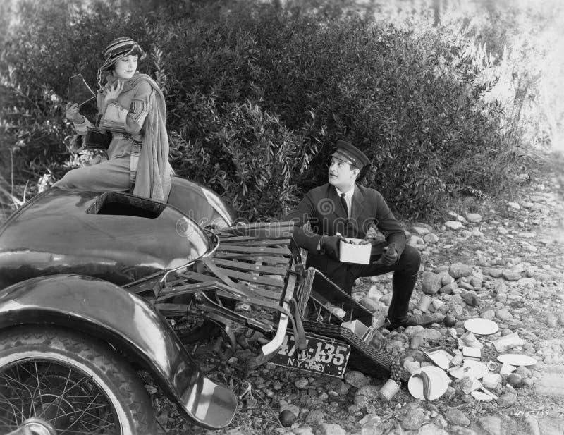 Kobieta i chauffer po tym jak wypadek samochodowy w kraju (Wszystkie persons przedstawiający no są długiego utrzymania i żadny ni obraz royalty free