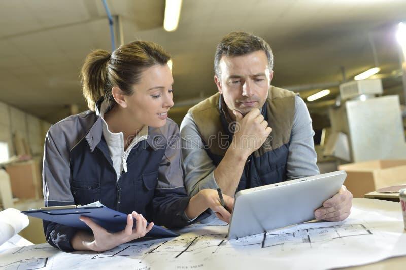 Kobieta i ciesielka instruktor dyskutuje i pracuje na pastylce obraz stock
