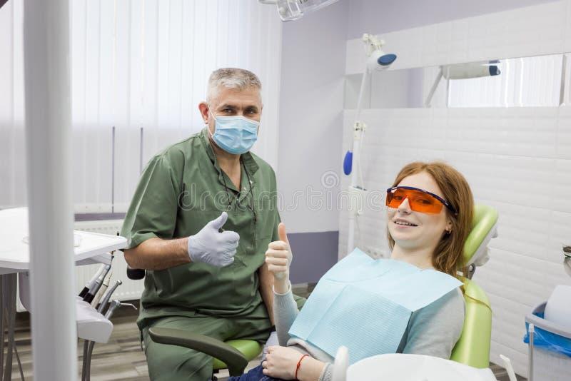 Kobieta i dentysta pokazuje kciuk up podpisujemy przy biurową kliniką obraz royalty free