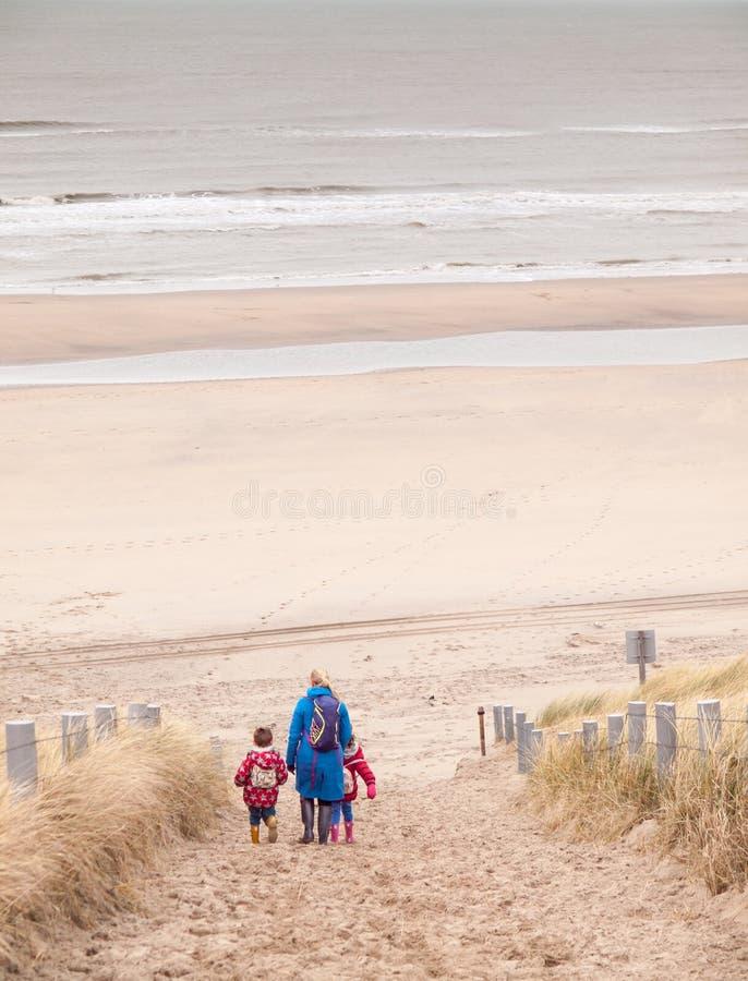 Kobieta i dwa małego dziecka chodzi w dół plaża zdjęcie royalty free