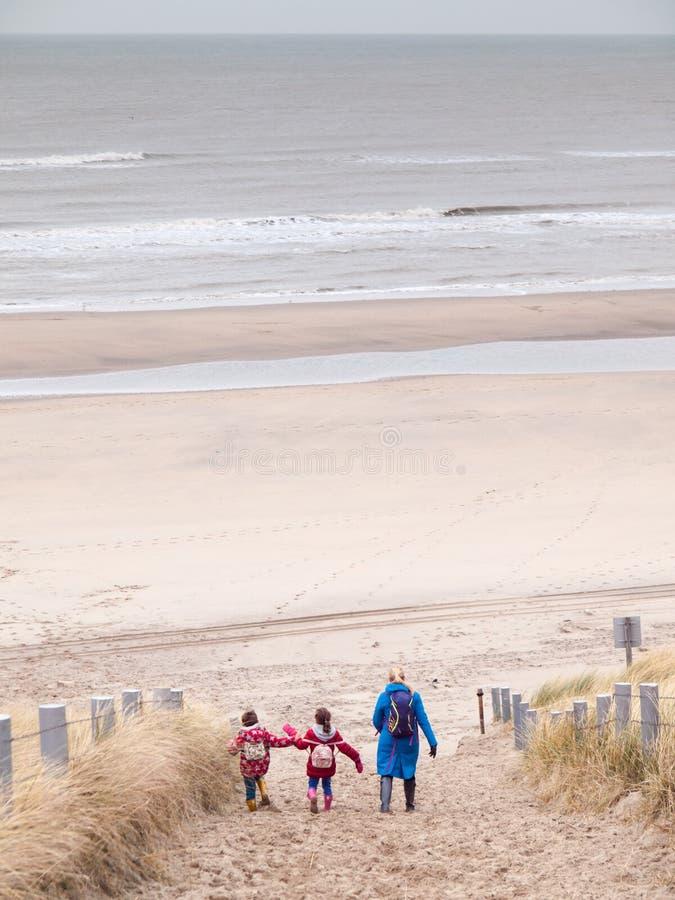 Kobieta i dwa małego dziecka chodzi w dół plaża obraz stock