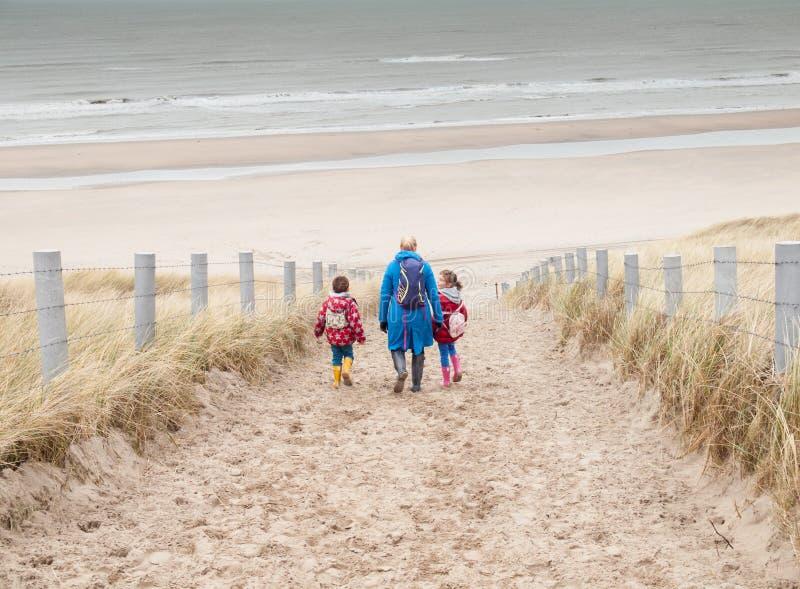 Kobieta i dwa małego dziecka chodzi w dół plaża zdjęcia stock