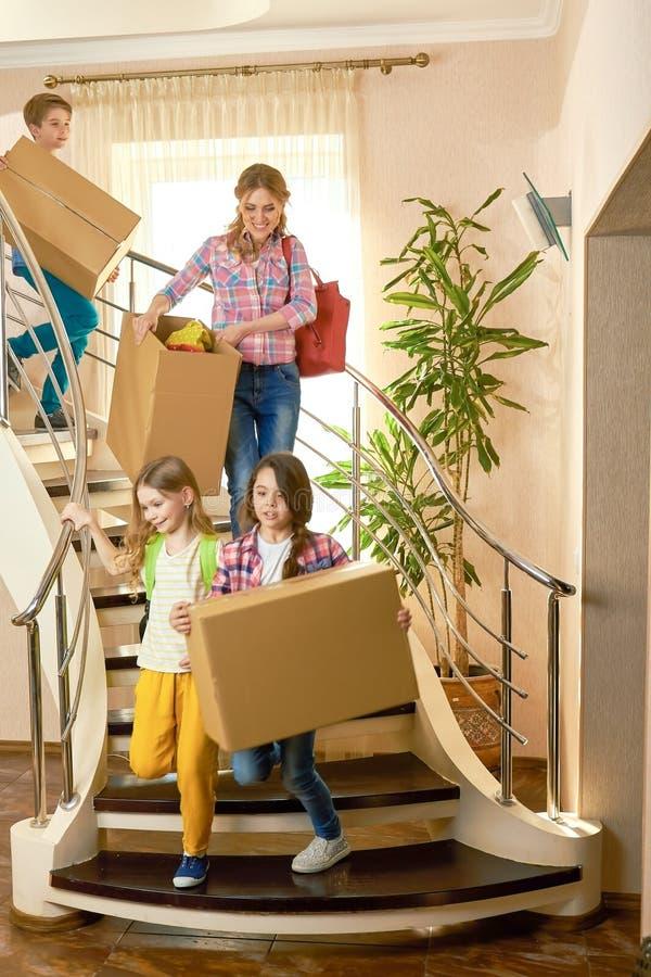 Kobieta i dzieci niesie pudełka obraz stock