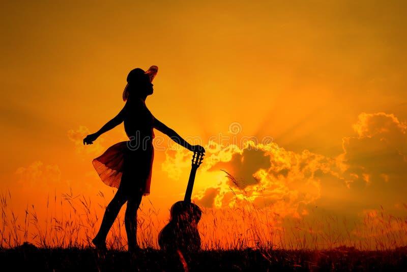 Kobieta i gitara z zmierzch sylwetką obraz royalty free