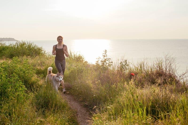 Kobieta i husky jogging na nadmorski obraz royalty free