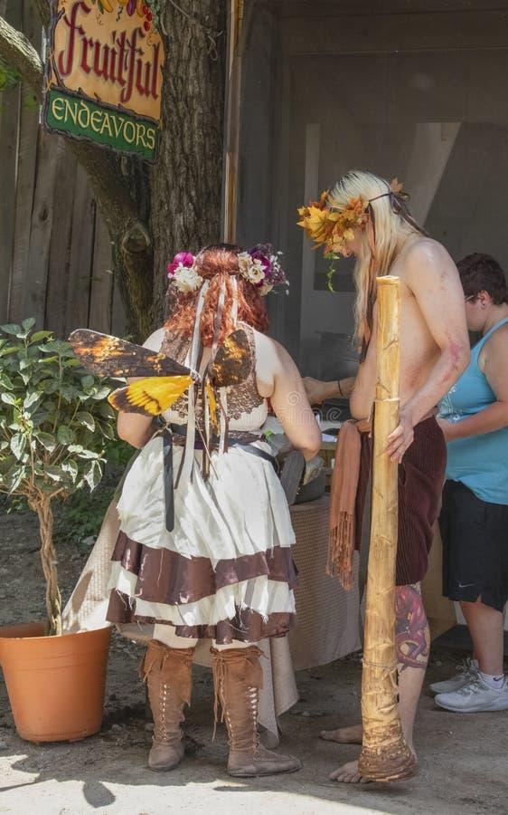 Kobieta i mężczyzna ubieraliśmy w fantazja kostiumu stojaku przygotowywać jedzenie w budka przy Renesansowym Faire w Muskogee Okl zdjęcie stock