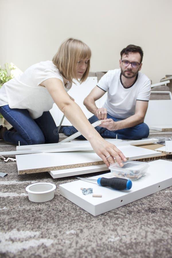 Kobieta i mężczyzna w cajgach i białych koszulkach siedzimy na dywanie w żywym pokoju mieszkanie i obracamy białego meble obrazy royalty free