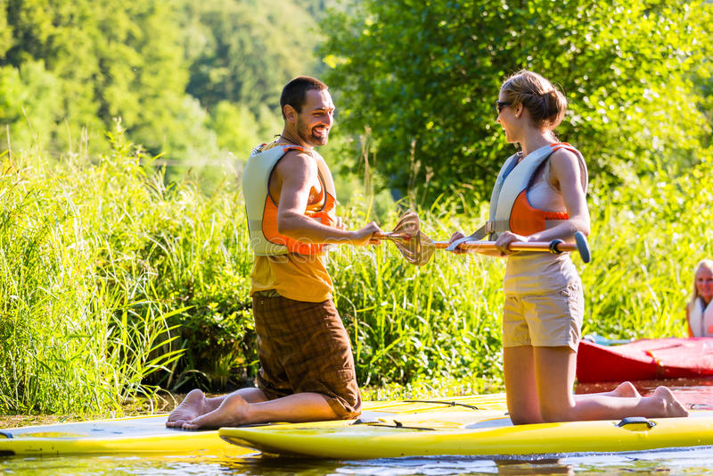 Kobieta i mężczyzna z stoimy up paddle deski sup na rzece zdjęcia royalty free