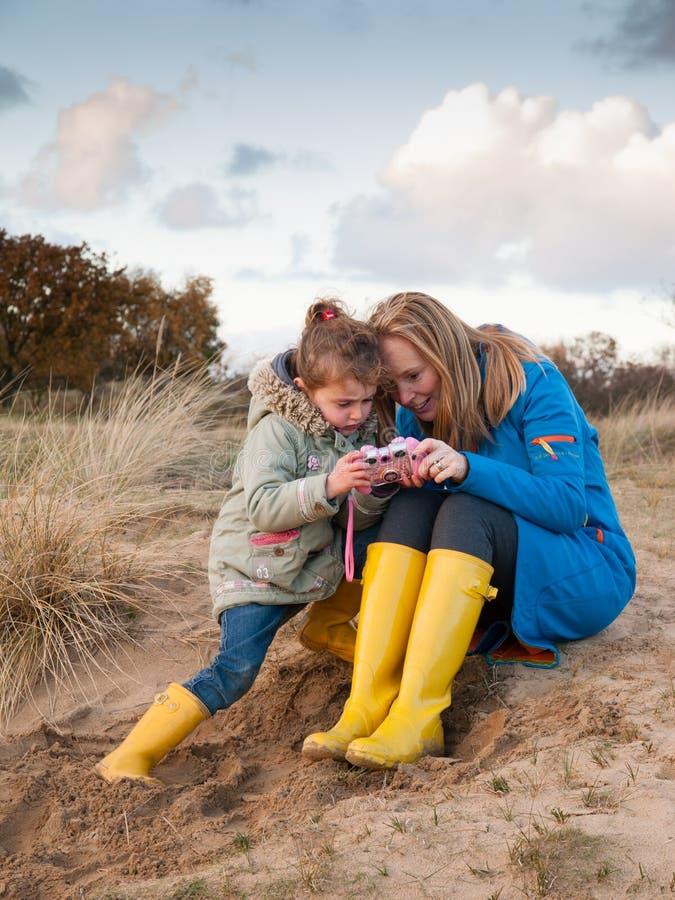 Kobieta i mała dziewczyna bawić się wpólnie w diuna krajobrazie obrazy stock