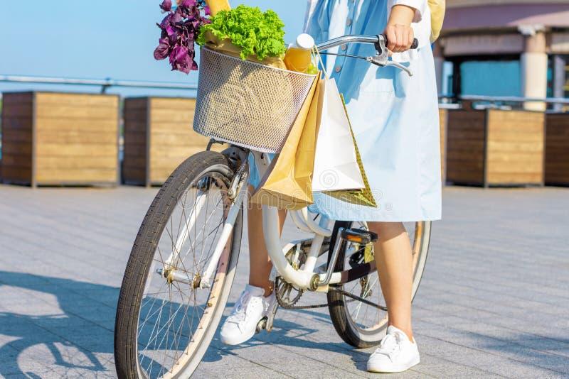 Kobieta i?? na piechot? w b??kit sukni na bia?ym bicyklu z koszykowy pe?nym warzywa obrazy stock