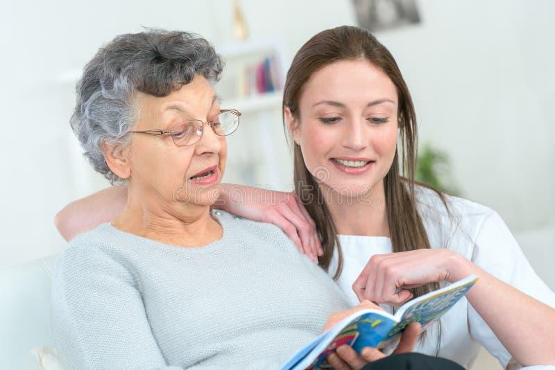 Kobieta i senior kobieta z książką w domu obraz stock