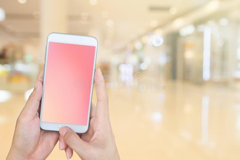 Kobieta i trzymać mądrze telefon z plama zakupy centrum handlowego backgrou obraz royalty free