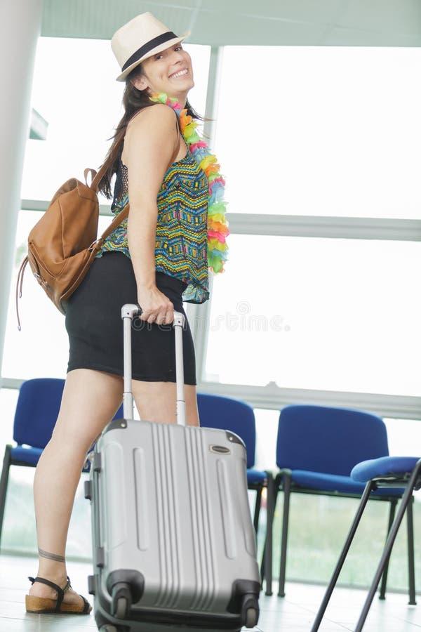Kobieta idzie na lotnisko w oknie z walizką zdjęcia royalty free