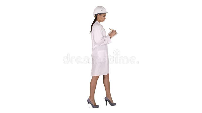 Kobieta inżynier z hełmem jest mienia piórem i listy kontrolnej kładzenie coś zestrzela podczas gdy chodzący na białym tle zdjęcie royalty free