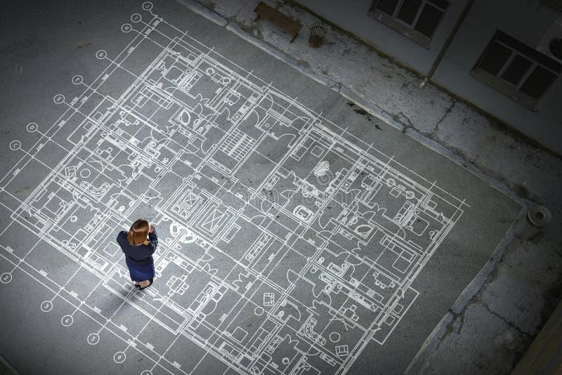 Kobieta inżynier myśleć nad jego planem Mieszani środki fotografia royalty free