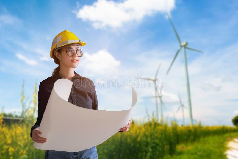 Kobieta inżynier patrzeje silniki wiatrowych na tle zdjęcia stock