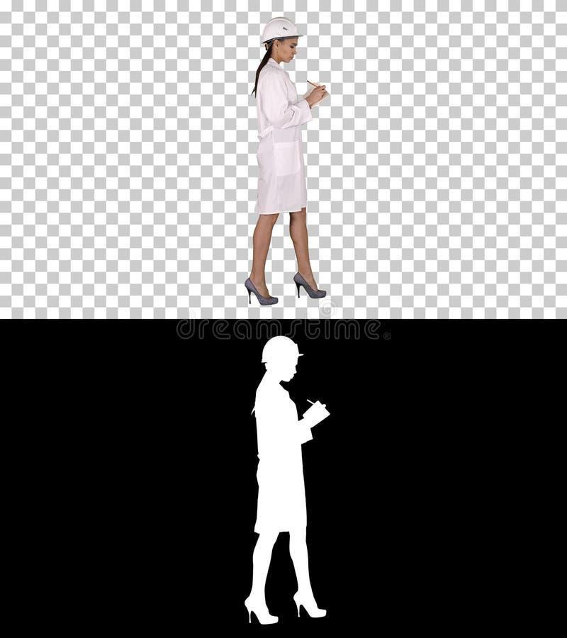 Kobieta inżynier z hełmem jest mienia piórem i listy kontrolnej kładzenie chodzący coś zestrzela podczas gdy, Alfa kanał zdjęcia stock