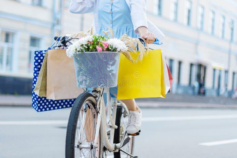 Kobieta jeździć na rowerze na białym bicyklu z pakunkami na handlebars fotografia royalty free