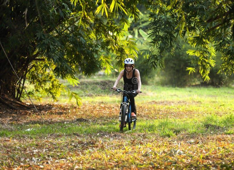 Kobieta jeździć na rowerze w parku obraz stock