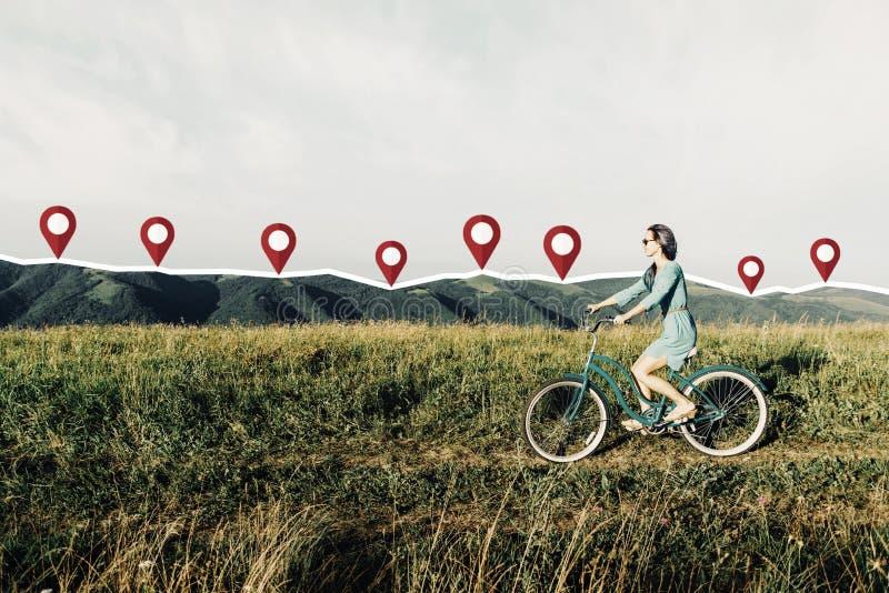 Kobieta jeździecki bicykl na łące z związanymi szpilkami fotografia stock