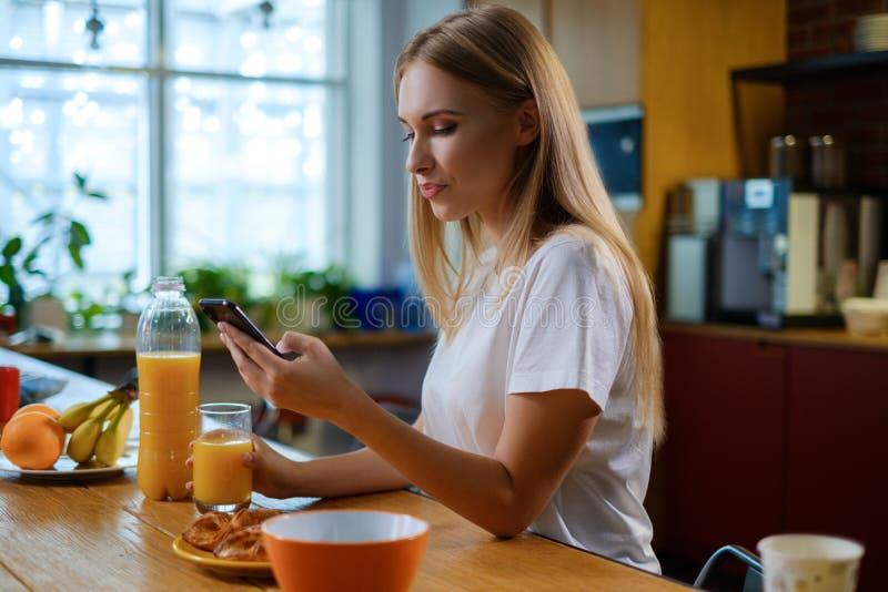 Kobieta je śniadanie i używa jej telefon komórkowego obraz royalty free