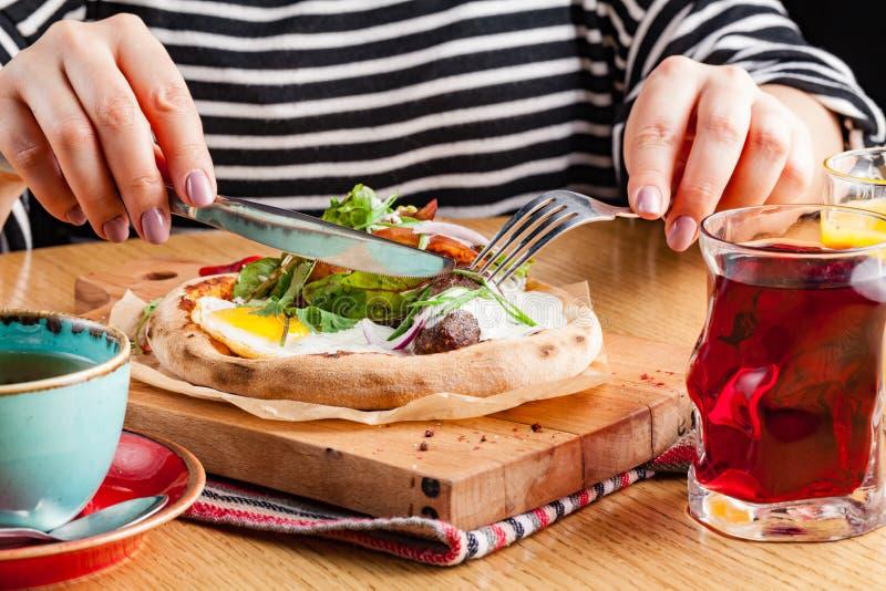 Kobieta je Angielskiego śniadanie rozdrapani jajka z bekonem, kiełbasami i warzywami, zbliżenie obrazy royalty free