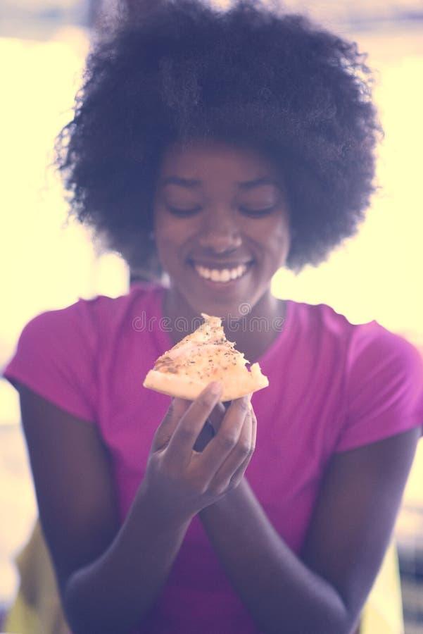 Kobieta je smakowitego pizza plasterek z afro fryzurą obrazy stock