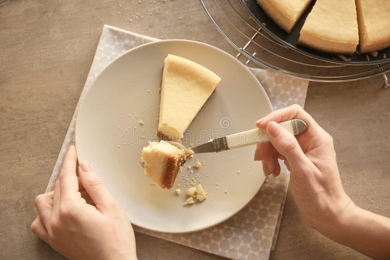 Kobieta je wyśmienicie cheesecake z łyżką zdjęcia stock