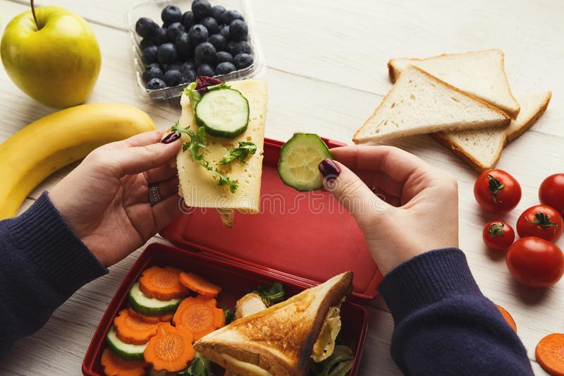 Kobieta je zdrową kanapkę od lunchu pudełka przy jej pracującym stołem obrazy stock