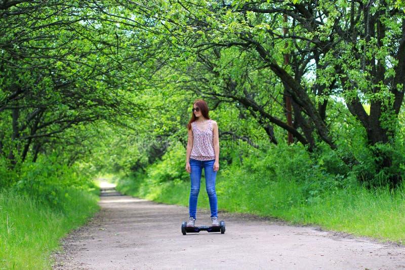 Kobieta jedzie elektryczną hulajnoga outdoors obraz stock