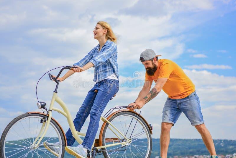 Kobieta jedzie rowerowego nieba tło Dlaczego uczyć się jechać rower jako dorosły Dziewczyny kolarstwo podczas gdy chłopak wspiera fotografia stock
