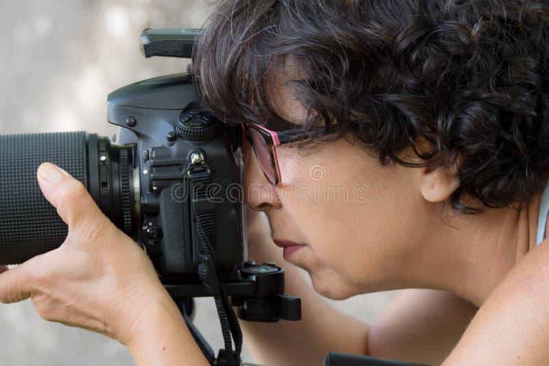 Kobieta jest fachowym fotografem z slr kamerą obraz royalty free