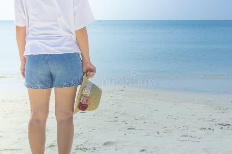 Kobieta jest ubranym białą koszulkę, stoi na piasek plaży i trzyma wyplata kapelusz w ręce, ona patrzeje niebieskie niebo i morze obraz stock