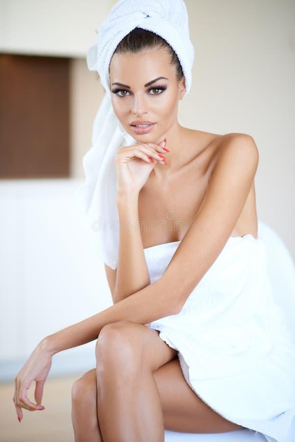 Kobieta Jest ubranym Białego Kąpielowego ręcznika z ręką na podbródku obraz royalty free