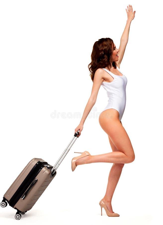 Kobieta jest ubranym białego swimsuit i pozycja z podróżą zdojesteśmy obrazy stock