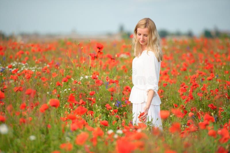 Kobieta jest ubranym bielu smokingowego kursowanie z czerwienią kwitnie w kwitnąć su fotografia stock
