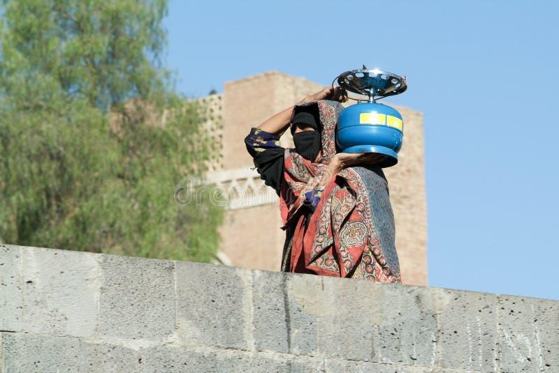 Kobieta jest ubranym burqa i niesie benzynową butlę obrazy royalty free