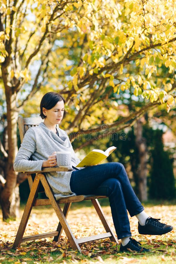 Kobieta jest ubranym ciepłą dzianinę odziewa pić filiżankę gorąca herbata lub cof zdjęcie royalty free
