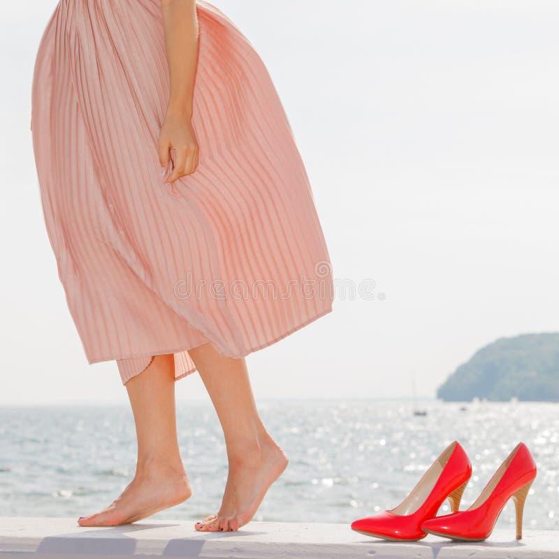 Kobieta jest ubranym długiego światło - różowa suknia na jetty fotografia royalty free