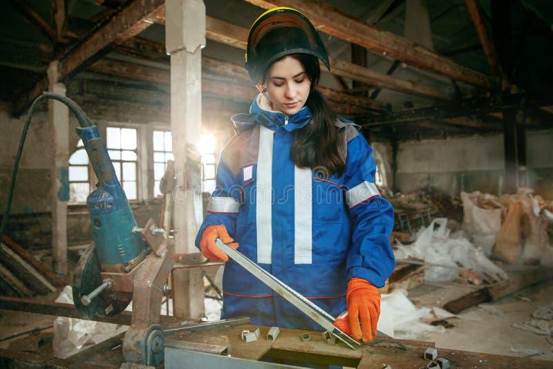 Kobieta jest ubranym hełm używać męskich prac narzędzia obrazy stock