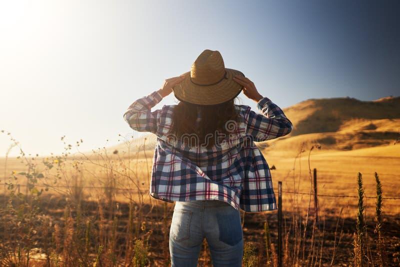Kobieta jest ubranym kapelusz za od patrzeć widok wiejski California krajobraz obraz stock