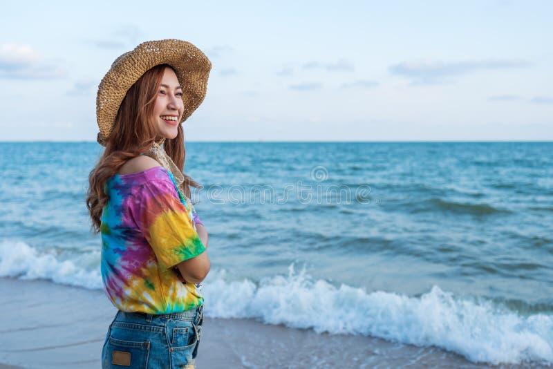 Kobieta jest ubranym kapeluszową pozycję na morze plaży fotografia royalty free