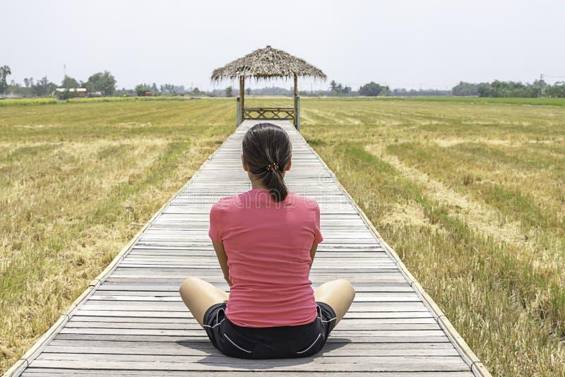 Kobieta jest ubranym Kapeluszowego obsiadanie na drewnianym mo?cie z bambusow? bud? w ry?owych polach obraz royalty free