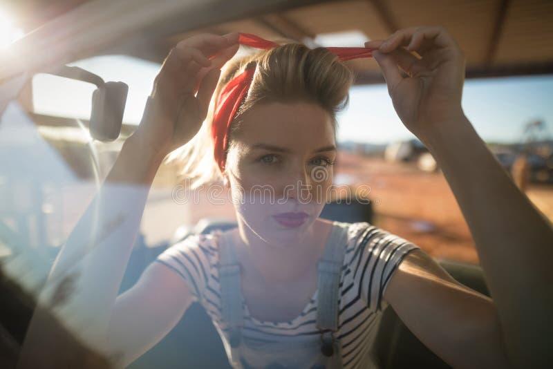 Kobieta jest ubranym kapitałkę w samochodzie obraz stock